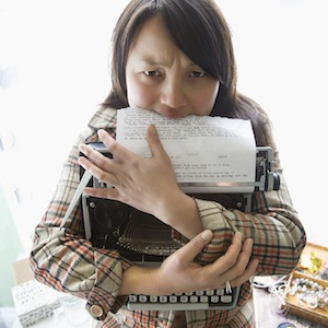 Pretty young Asian woman holding typewriter and biting page.